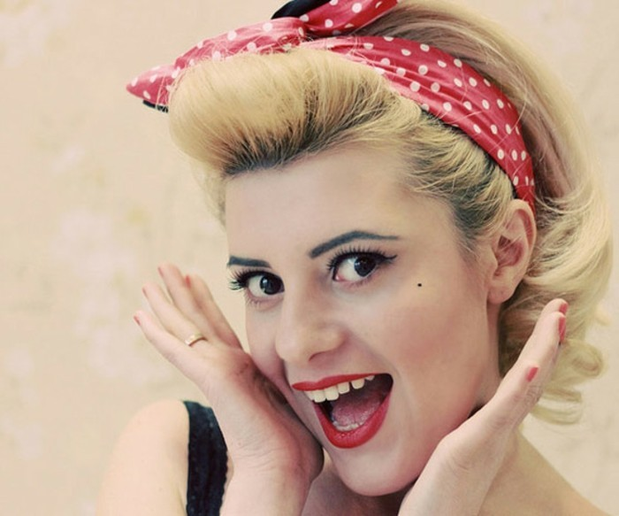 close up of happy smiling woman, open month white teeth and red lipstick, black eyes fake lashes eyeliner and mascara, dyed blonde hair red bandanna with white polka dots