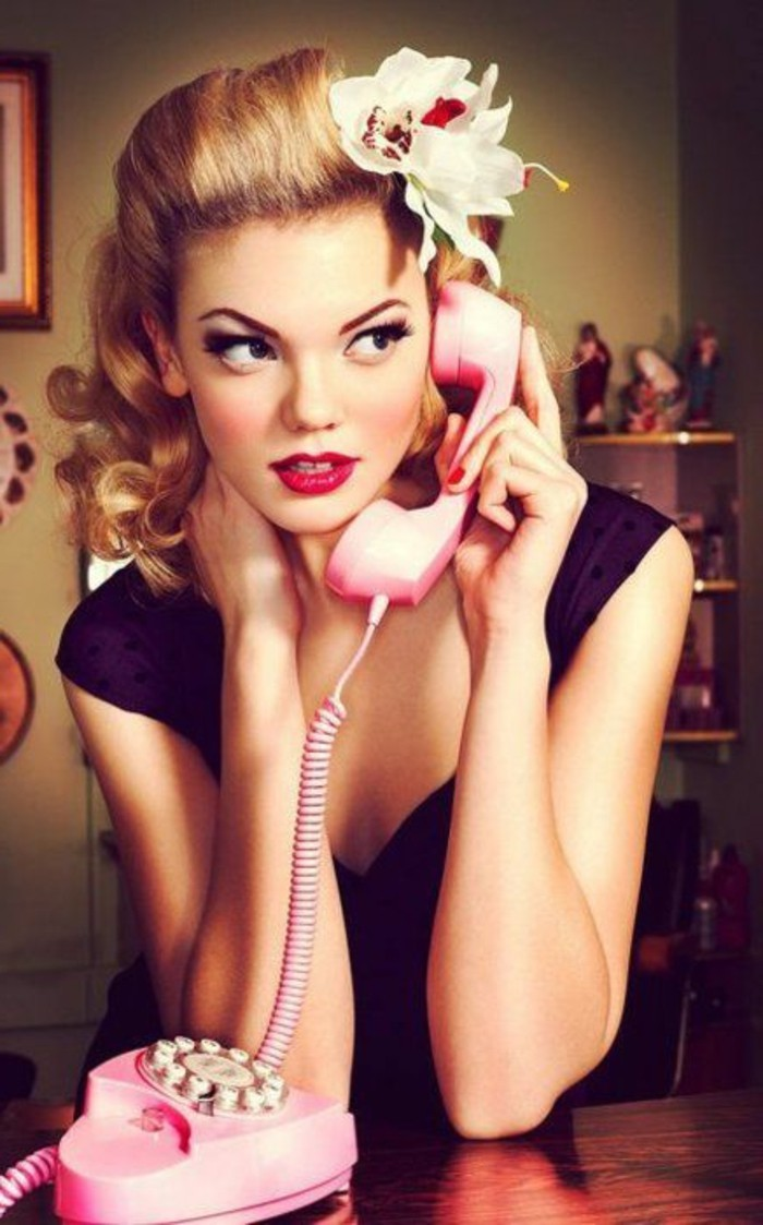 pinup style, blonde woman with fake white flower in hair, heavy make up bright red lipstick, dark black eye makeup with mascara an eyeliner, black top and red nail polish, holding a pink telephone receiver