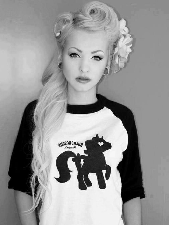 pinned up hairstyles for long hair, platinum blonde young woman with heavy make up and flesh earrings, three fake flowers in hair, black and white pony t-shirt