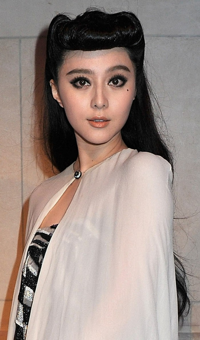 pinned up hairstyles for long hair, east asian woman with long black hair and curled bangs, black eyes with fake eyelashes mascara and eyeliner, beauty spot and nude-colored lipstick, white cardigan and a striped top