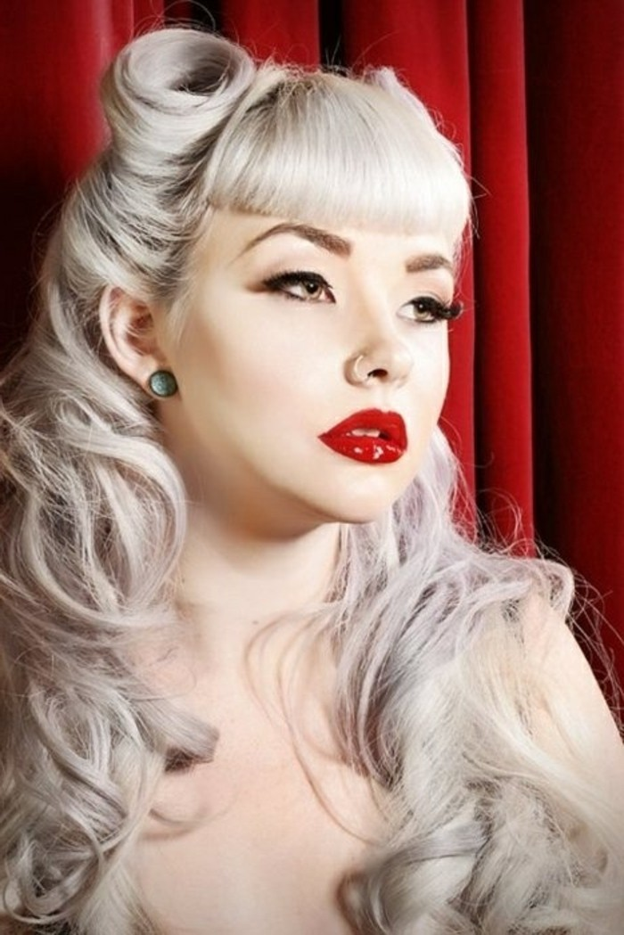 betty bangs, woman with long platinum blonde hair, victory rolls curls and bangs, nude shoulders a nose ring and green stud earrings, red lipstick fake lashes mascara