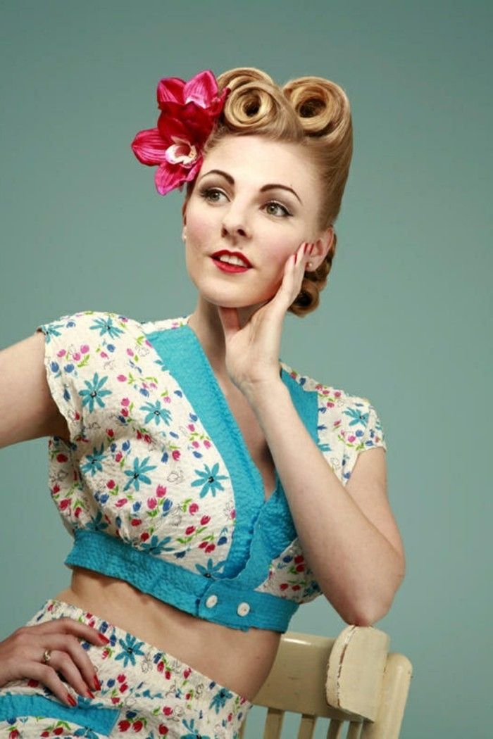 blonde woman leaning on white chair, hair styled in three victory rolls with two fake pink tropical flowers, wearing a two piece suit in white and blue