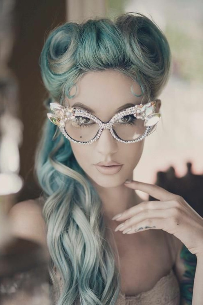 rockabilly hairstyles, woman with long light blue hair victory rolls and curls, wearing decorative glasses with rhinestone studded frames, mustache finger tattoo