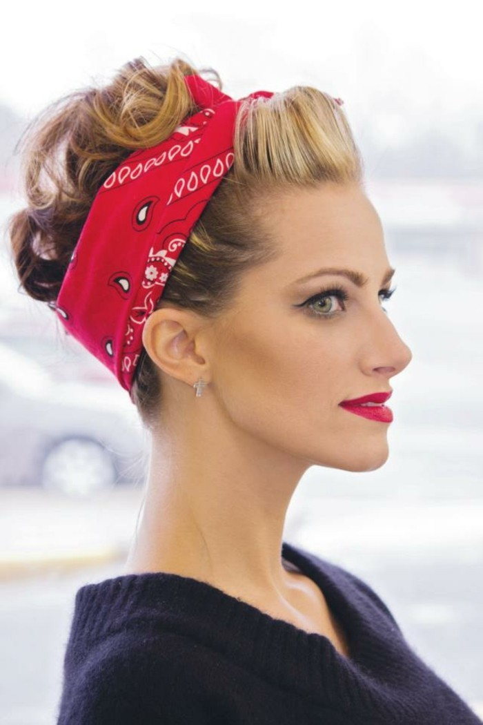 pin up hairstyles, close up of woman in profile, blond hair with curls tied with a red bandanna, red lipstick eyeliner and fake lashes, navy sweater and light background