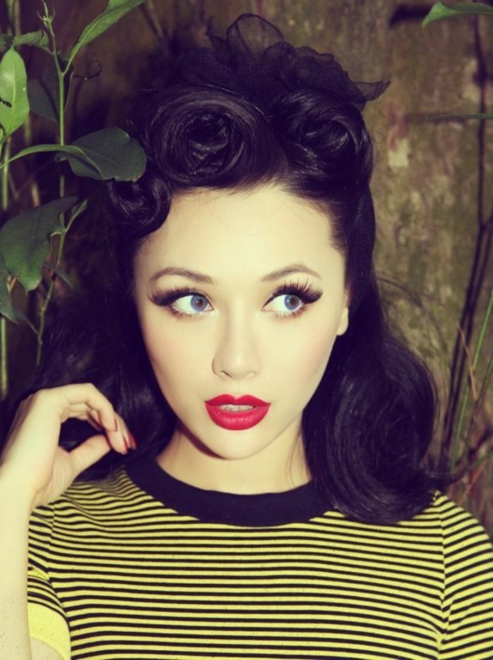 rockabilly hair, pale girl with dark hair done in retro victory rolls, with red lipstick and nail polish, big fake eyelashes with mascara and eye liner, yellow top with black stripes