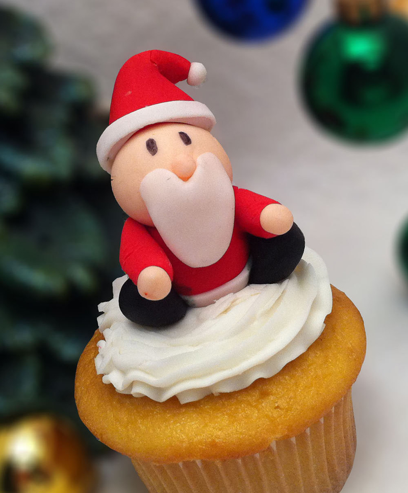 close up of small plain cupcake with white icing, decorated with small and simple red, black orange and white santa fondant shape