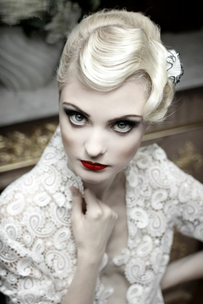 pin up girl hairstyles, retro 1920's short wavy hairstyle, worn by pale platinum blonde woman, with heavy eye make up red blush and lipstick, white paisley lace top