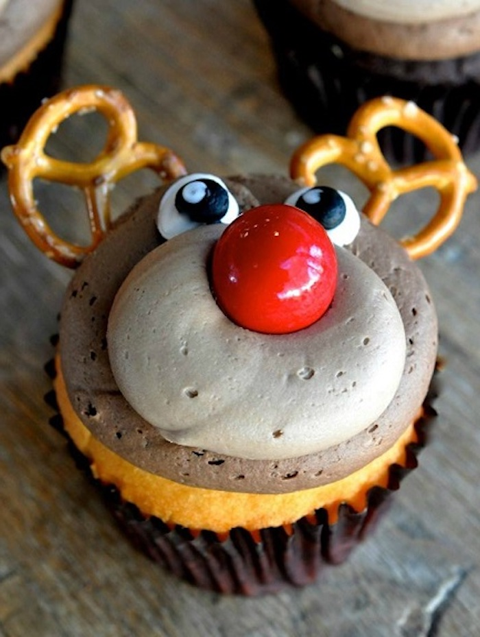 close up of a cupcake with brown icing, made to look like rudolph, with pretzels for antlers, big red candy for nose and frosted eyes