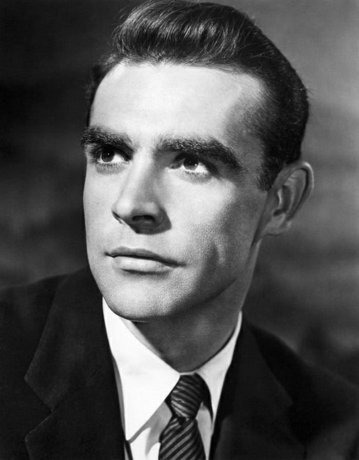 black and white photo of young sean connery, black blazer and white shirt, striped tie and gelled up hair, grey background
