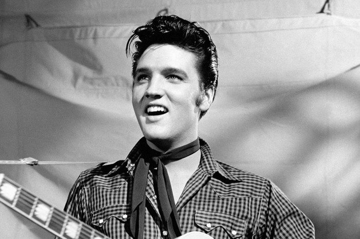 grey scale photo of young elvis presley, gelled up shiny black hair, smiling or singing, chequered shirt with pockets and small narrow black scarf tied around neck