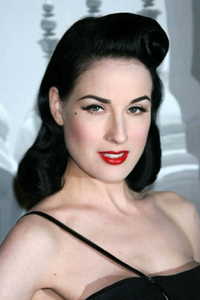 pinned up hairstyles for long hair, dita von teese, black long hair with rolled back bangs, red lipstick blush eyeliner fake lashes and mascara, black top with one strap