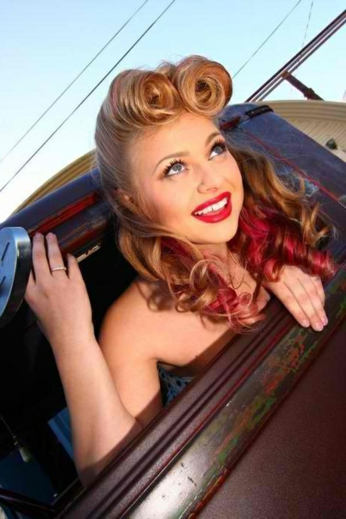 woman with victory rolls and curly blonde hair with red streaks, red lipstick and white teeth, blue eyes fake eyelashes mascara and eyeliner, nude shoulders looking out from a car window