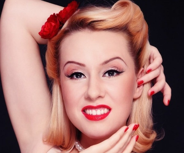 close up of a blonde woman, with fake eyelashes and black eyeliner, big white teeth and red lipstick,1950's style shoulder-length hair, two red fake flowers, pearl necklace and hands near face