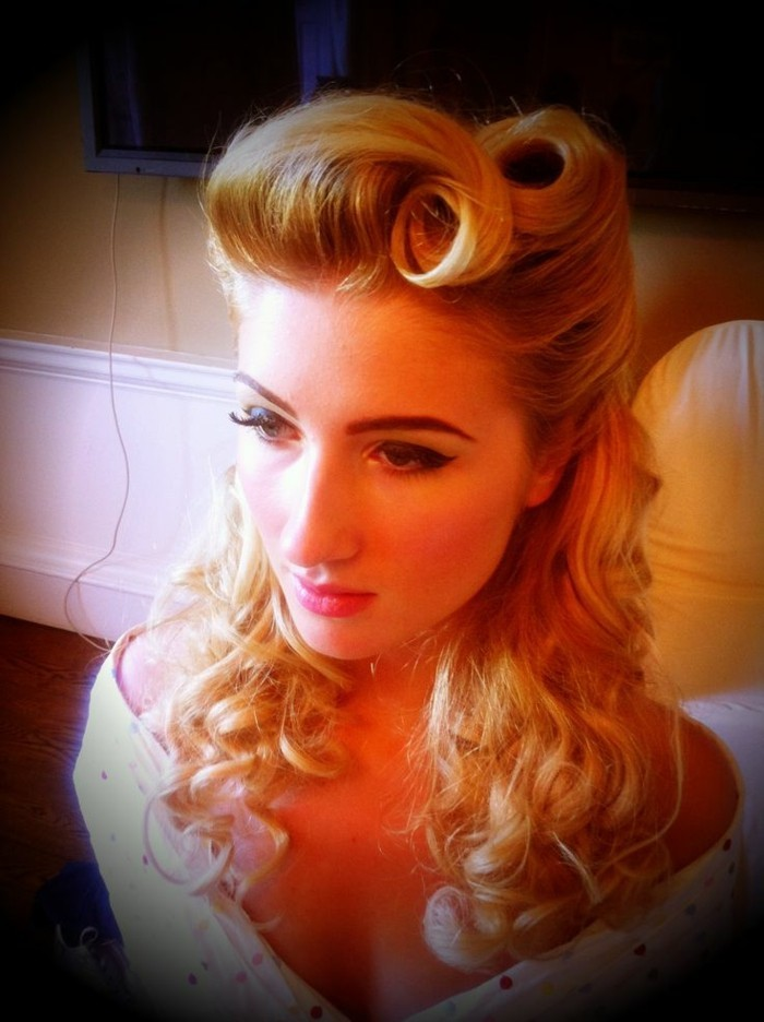 blonde woman seen from above, wearing heavy mascara and fake lashes, curled shoulder-length hair and victory rolls, white top and dark filter