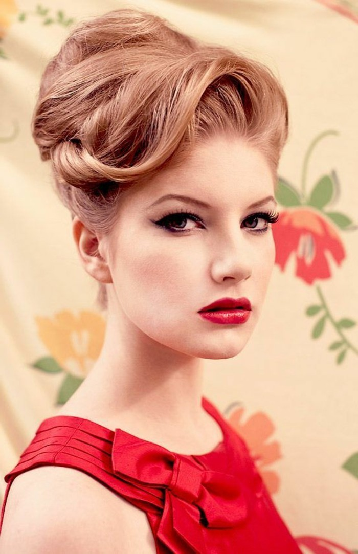 rockabilly hairstyles, close up of a woman with ginger hair in fancy retro 1950's undo, red top with bow, red lipstick fake lashes and eyeliner