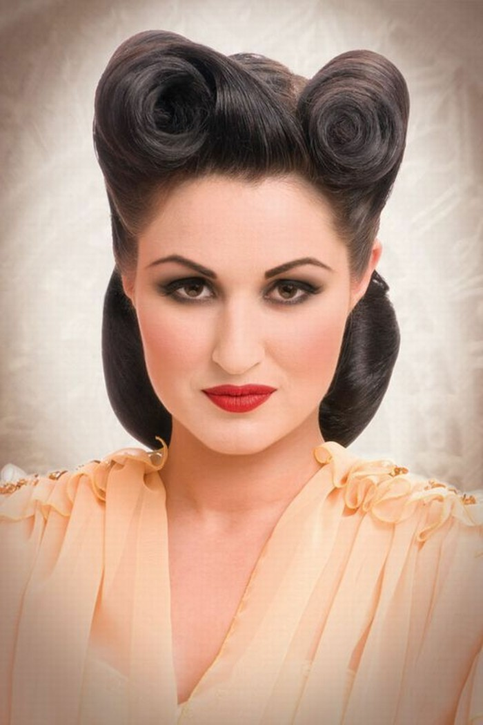 dark-haired woman with hair styled up in victory rolls, dark eye make up with eyeliner and mascara, peach-colored chiffon top, bright red lipstick and blush