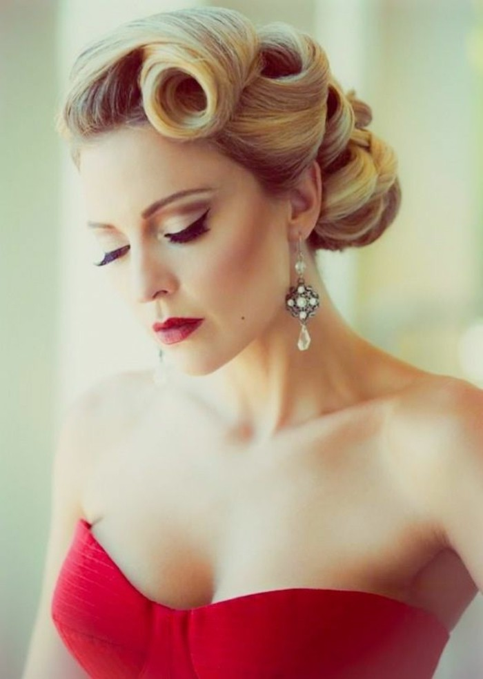 serious-looking woman with blonde hair with retro victory curls, pearl earrings and a red strapless top, red lipstick fake eyelashes and eyeliner
