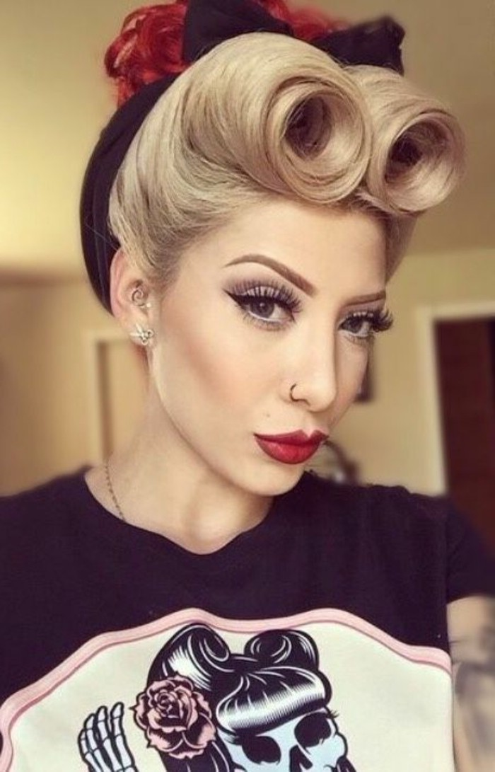 pouting blonde woman with blonde hair, styled in victory rolls with black hair bow, curly hair bun dyed in red, heavy make up with big fake lashes and black eyeliner