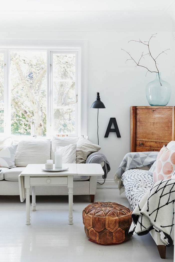 living room paint colors, room with white walls and windowpanes, wooden cupboard with big clear blue vase containing small branch, white sofa and table, cushions and blankets of different colors, brown basket with lid