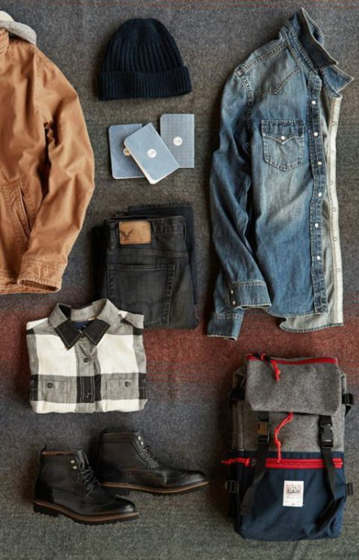 business casual outfits, light brown men's jacket, near folded black jeans, folded black white and gray chequered shirt, a pair of black lace up ankle boots, navy blue grey and red backpack, folded denim shirt and navy beanie hat