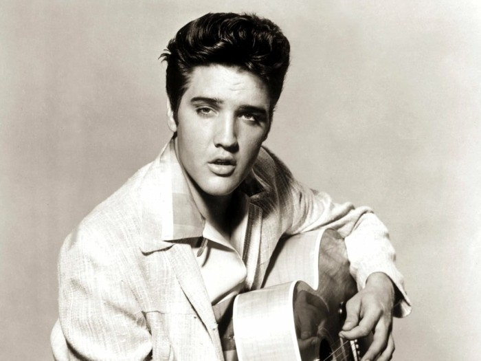 vintage black and white photo of elvis presley, light blazer and shirt with big collar, gelled up wavy hair, holding acoustic guitar with fingers on strings