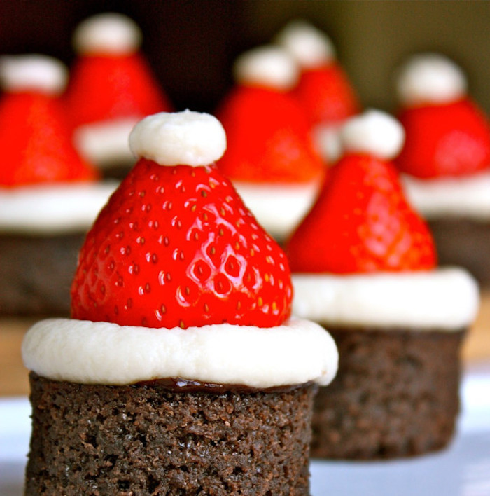 a batch of brownies, decorated with little santa hats, made from strawberries and cream