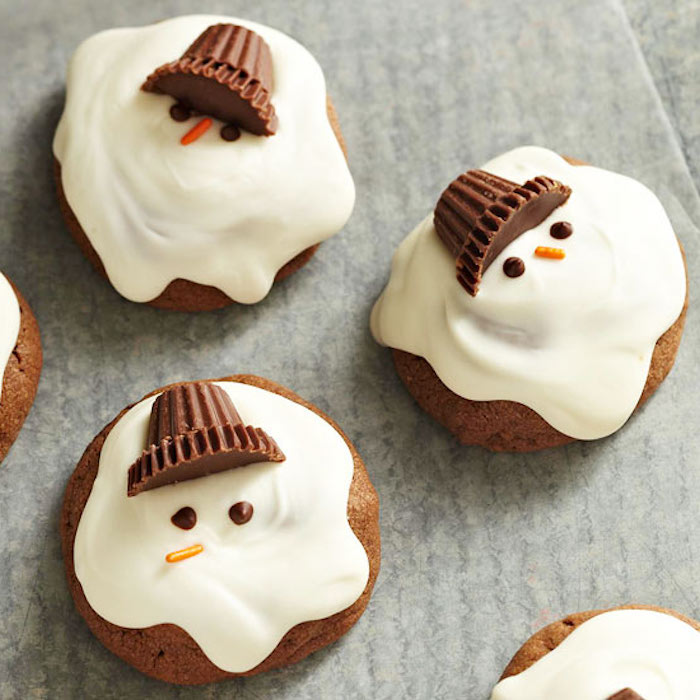 several cupcakes with white frosting, made to look like melting snowmen, with chocolate candies for caps