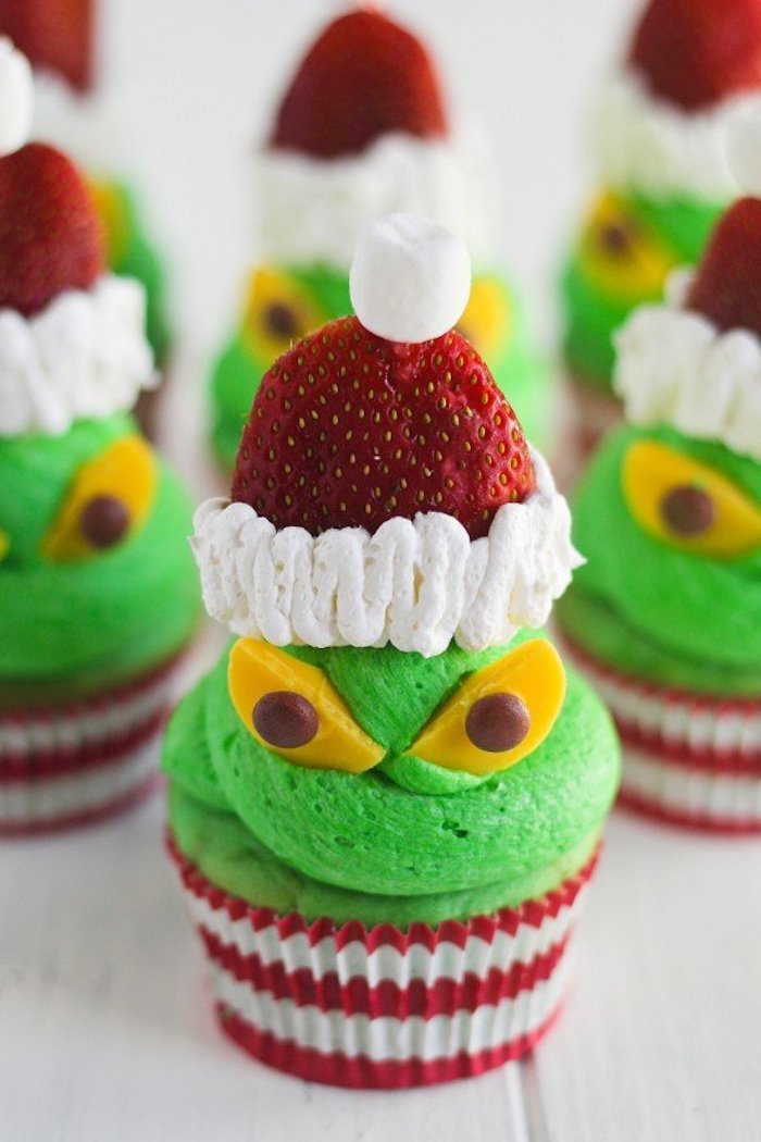 holiday cupcakes, a batch of cupcakes with acid green frosting, decorated with strawberries and cream, yellow and chocolate candies