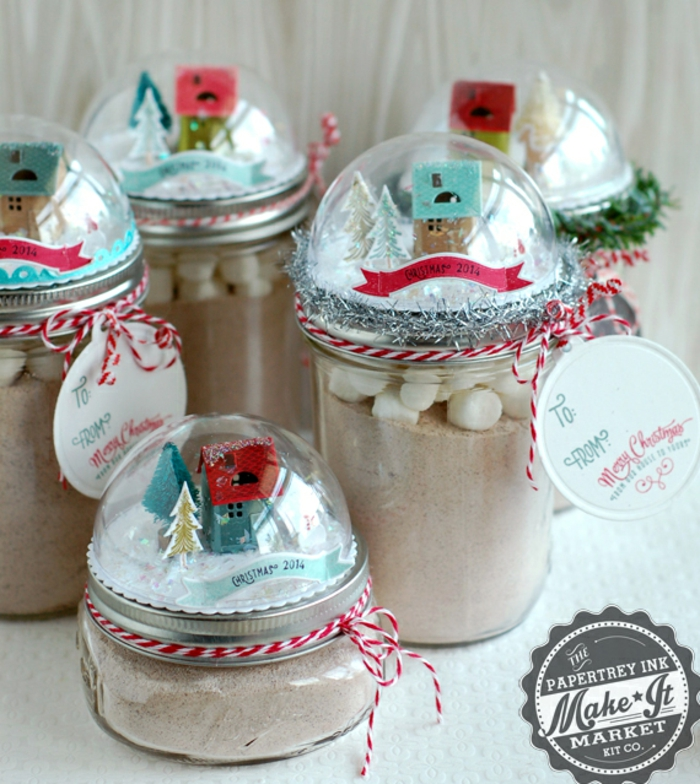 diy gift ideas, several jars of different sizes, filled with cocoa and marshmallows, with snow globes on their lids featuring little house figurines and colorful strips of paper