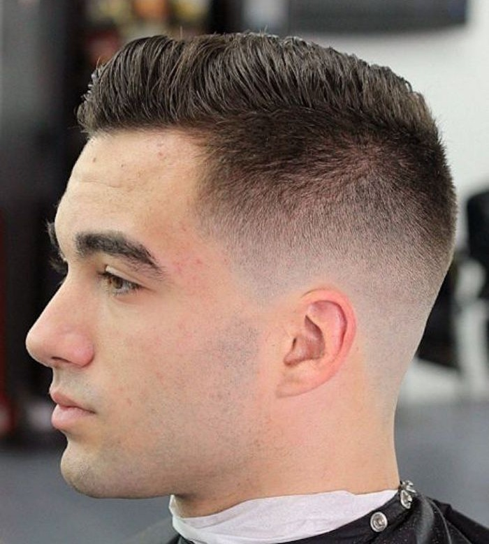slicked back undercut, serious looking man facing sideways, with serious expression, hair brushed back, short on sides and long on top