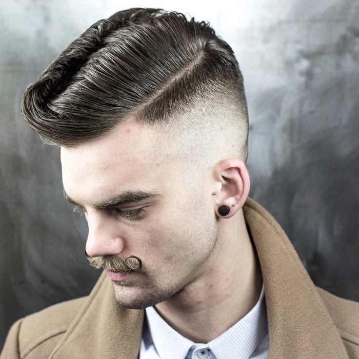 short hair on sides long on top, man with twisted up mustache, white shirt and camel coat, looking sideways down, with three earrings and hair shaven on the side and longer, combed over on top