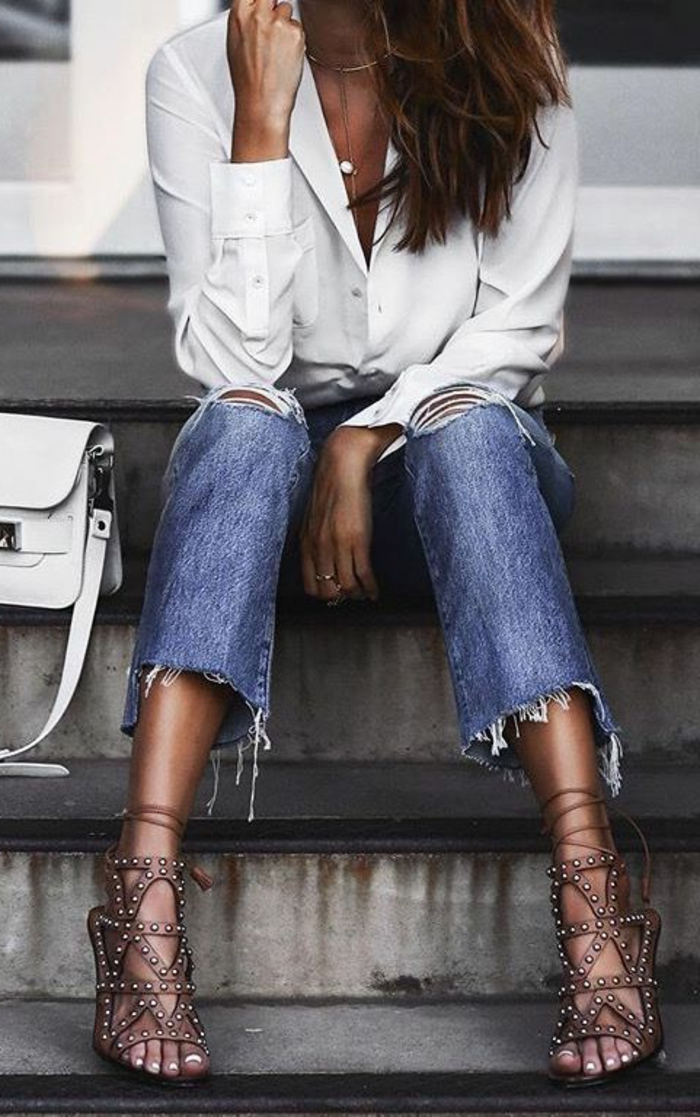 close up of female torso, sitting on steps and wearing cut-off ankle jeans, white formal shirt and strappy brown sandals with studs