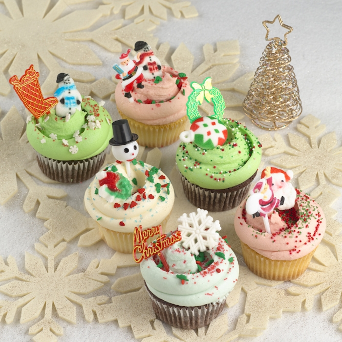 mini cupcake recipes, six chocolate and vanilla cupcakes, with pale blue pale pink and pale green frosting, decorated with christmas-themed shapes, near a small golden christmas tree ornament