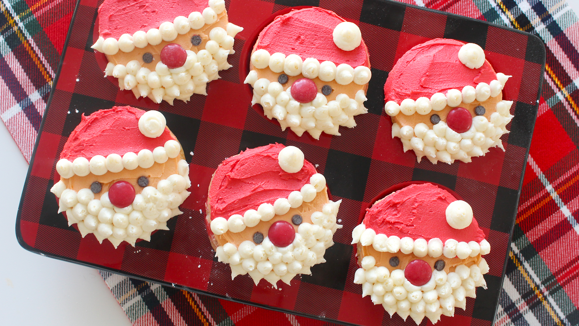 six cupcakes on red and black checkered muffin mould, decorated with red white and orange frosting, made to look like santa, red candies for noses