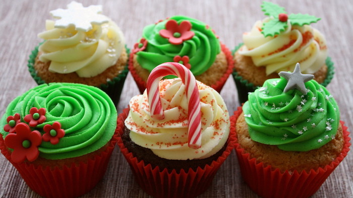 christmas cupcakes, six cupcakes with white or green frosting, decorated with christmas-themed fondant shapes