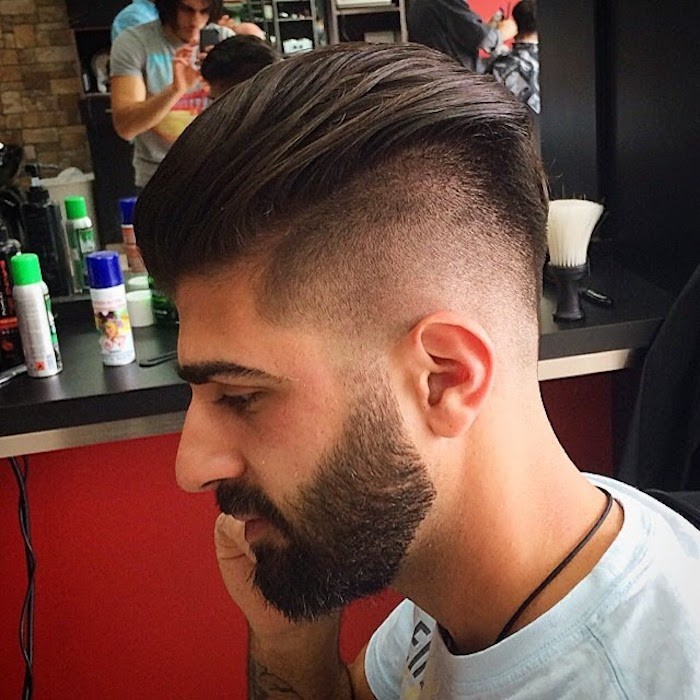 slicked back undercut, middle eastern man with beard and mustache, dark hair trimmed very short on sides and long, slicked back on top, facing sideways and wearing light t-shirt