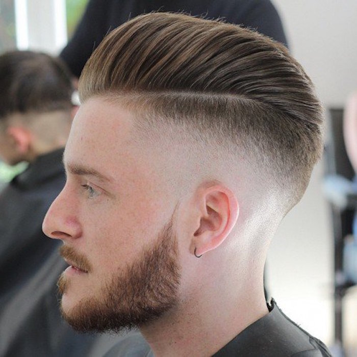 how to style a undercut, close up of a fair-haired man in profile, trimmed beard and mustache, small earring and hair cut short on the side and kept long on top