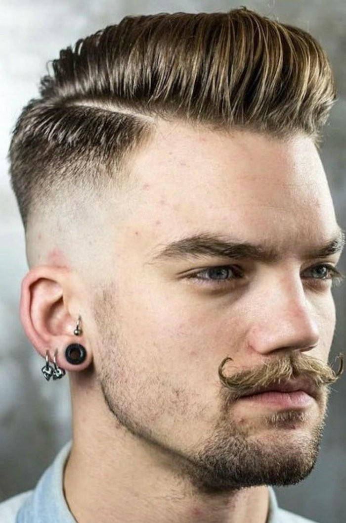 side part undercut, man with fair hair and twisted up mustache, stubble on chin and three earnings, one flesh earring and pale top, hair parted on the side, longer on top but shaven on sides