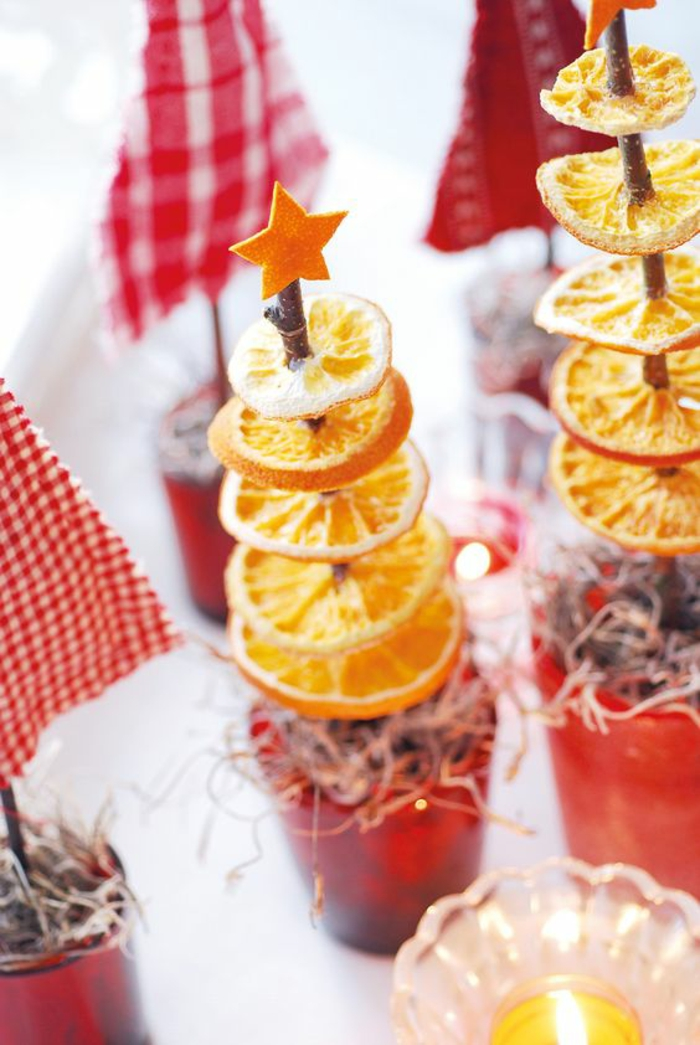 diy christmas gifts, two christmas tree ornaments, made from dried orange slices spiked on a twig, with little orange cut out star on top, near other decorations, small candle