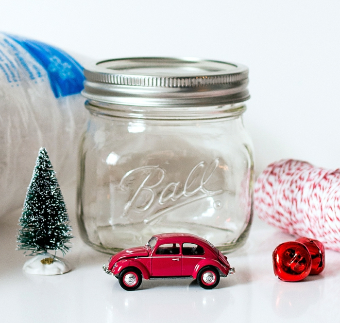 diy gift ideas, two small red bells, Christmas tree figurine and a red toy car, empty clear jar with screw lid, bag of fake snow and red and some white string
