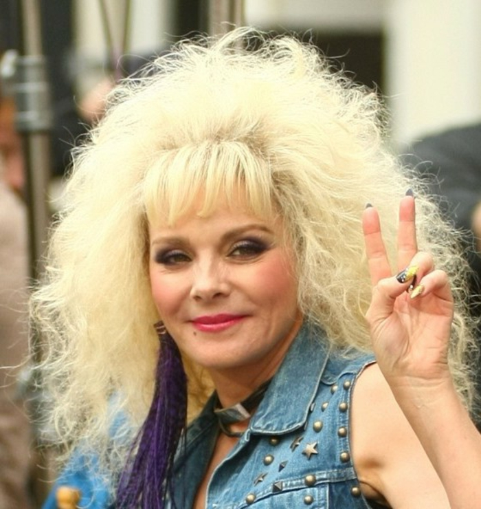 80s fashion trends, Kim Cattrall with big bleached feathery hair perm, star studded denim gilet, choker and big purple earring with tassels, holding a peace sign