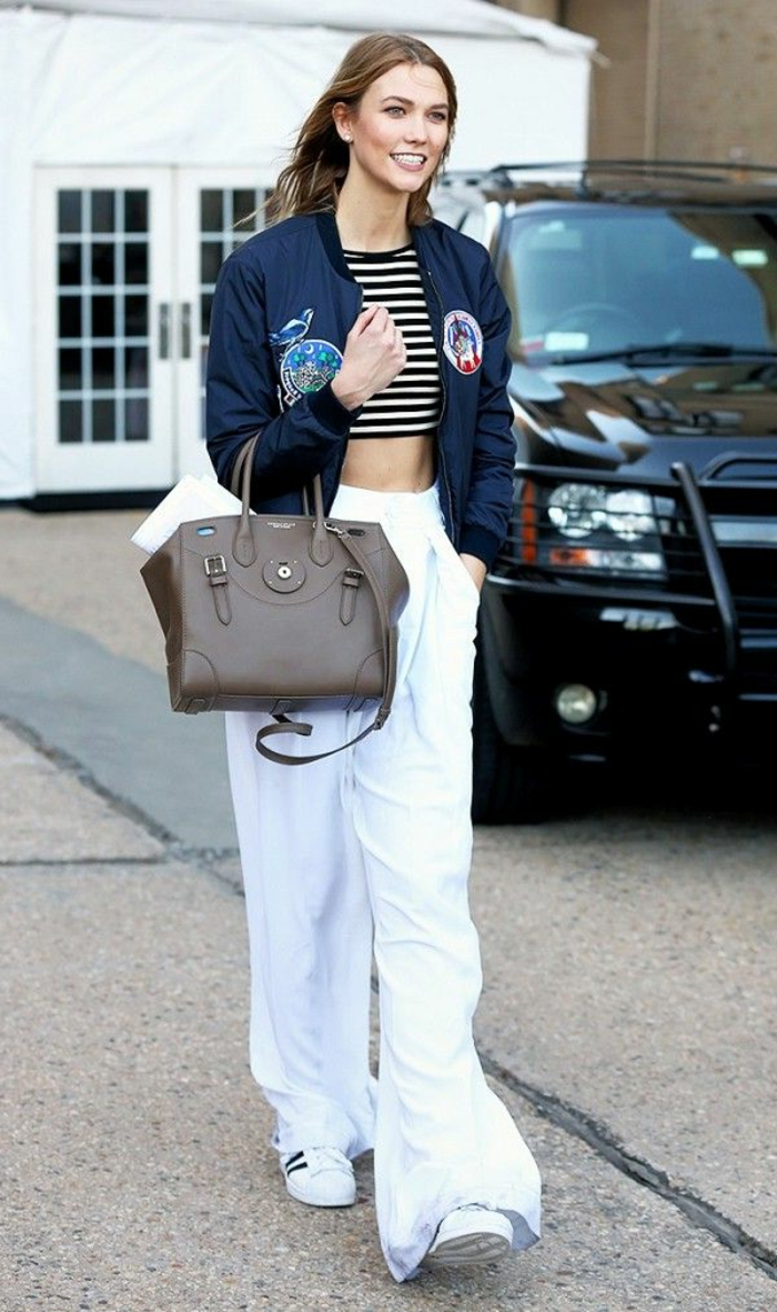 karlie kloss wearing long white sweatpants, black and white striped crop top, dark blue bomber jacket with patches, brown leather bag and white sneakers
