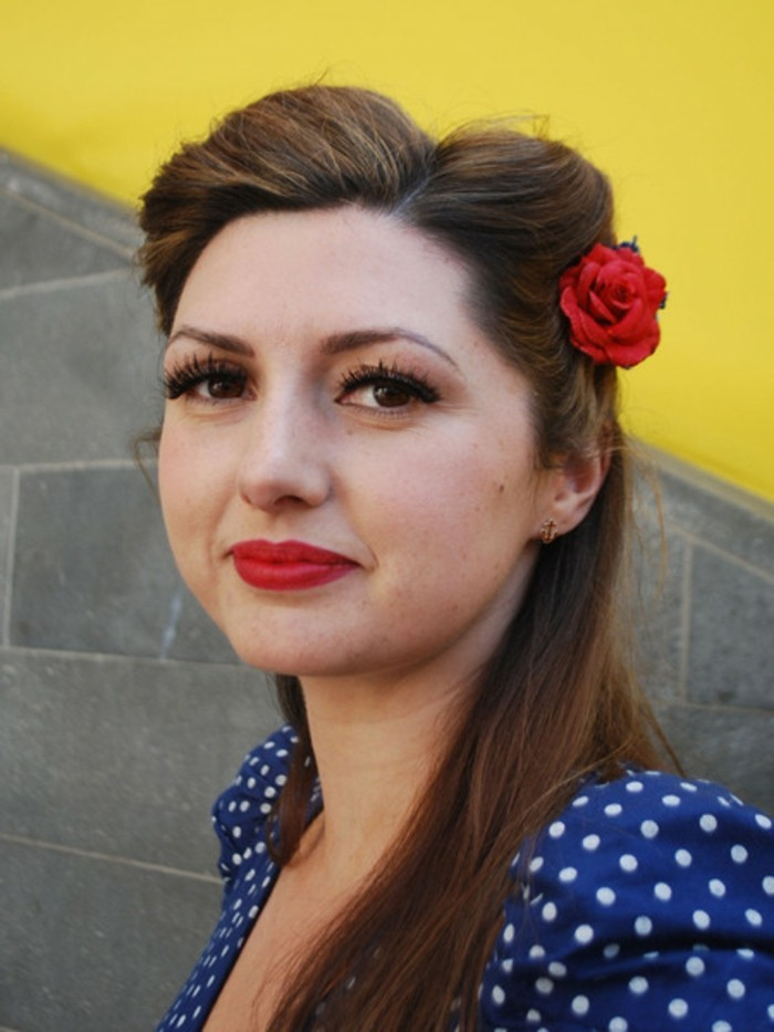 pinned up hairstyles for long hair, woman wearing a blue top with white polka dots, brown hair with retro twist and a fake red flower, fake eyelashes mascara eyeliner and red lipstick