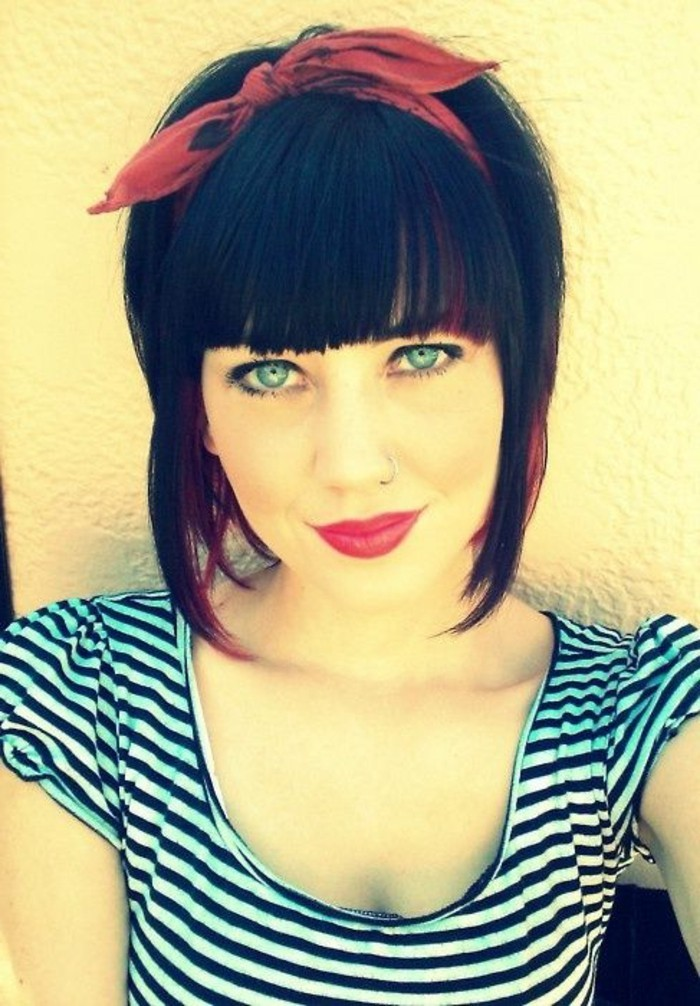 smiling woman with blue eyes and a retro hairstyle, bangs and a red bandanna, wearing a white and black striped top, black eyeliner and mascara yellow filter