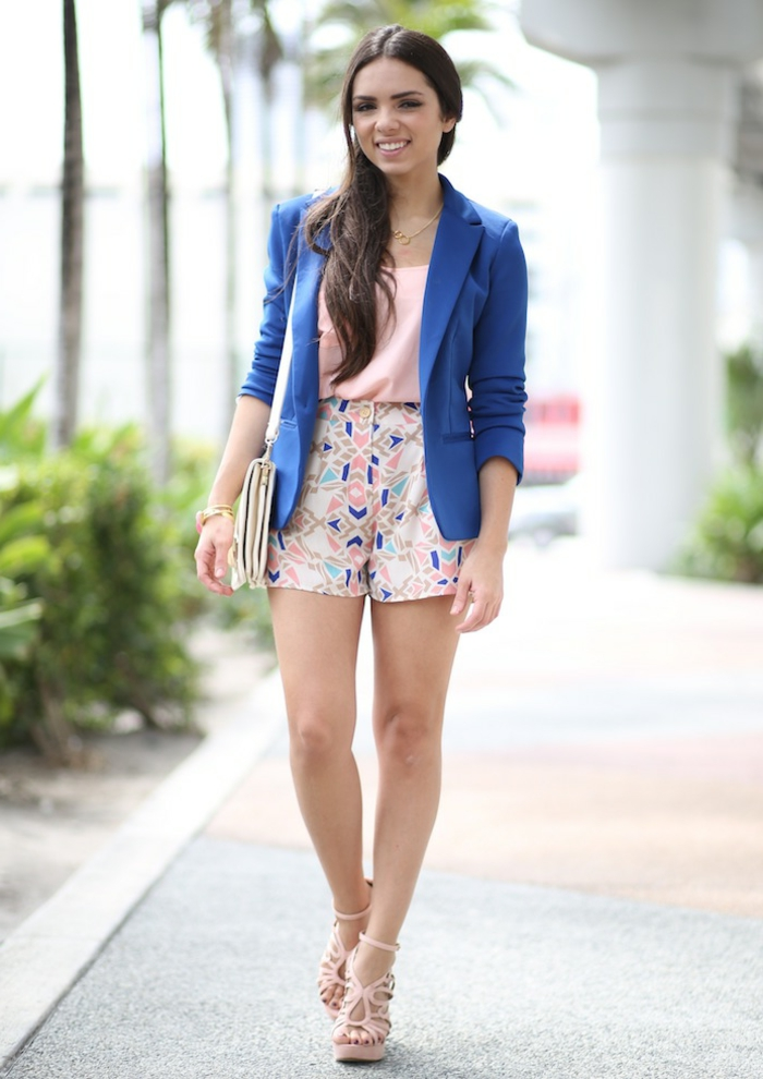 colorful high-waisted shorts in pale pink white and dark blue, combined with pink top and bright blue blazer, worn by brunette woman with pink high-heeled sandals