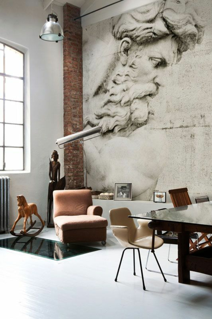 paint colors for living room, white floor and wall, big mural of statue and brick wall detail, wooden african statute and rocking horse, pale brown chair, massive wooden table with glass surfaces, cream chair and window