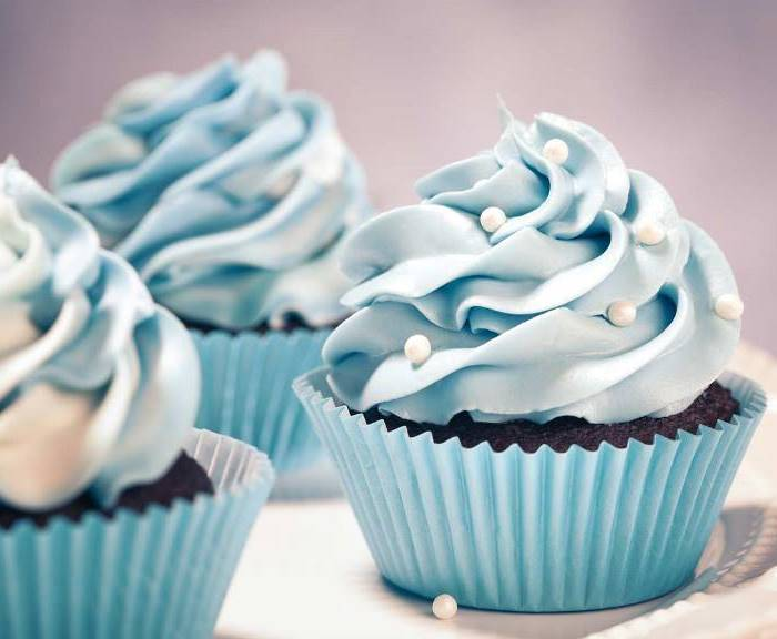 christmas baking ideas, three chocolate cupcakes in light blue wrappers, with light blue creamy frosting, decorated with white pearls