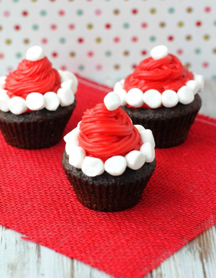 chocolate cupcakes images, three chocolate cupcakes, decorated with santa hats, made from red icing and small white marshmallows