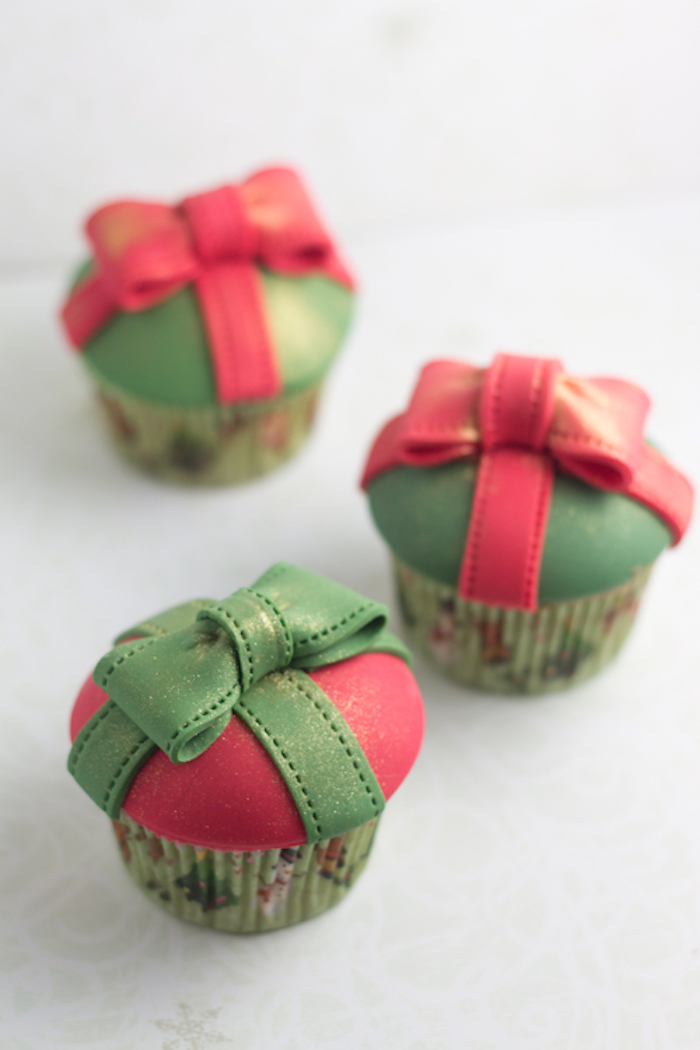 three cupcakes in green festive wrappers, green or red fondant frosting, red or green fondant bows on top, pale background