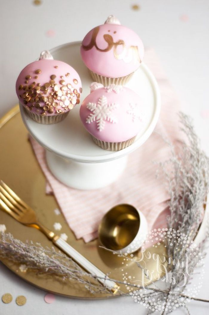three cupcakes with pink fondant frosting, decorated with golden letters and sprinkles, and white snowflakes, on white dish and golden tray